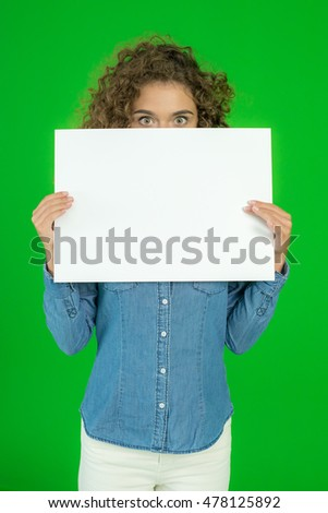 The young woman show empty sheet of paper the green background