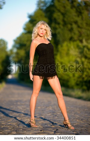The young woman stands on the paved road. - stock photo