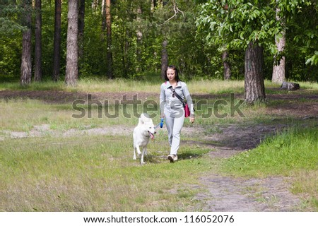 The young woman walks in park with a dog
