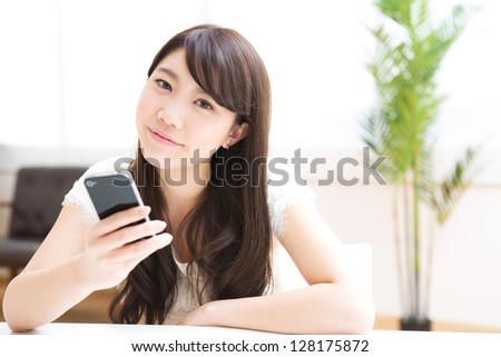The Young woman who uses the smart phone in a room