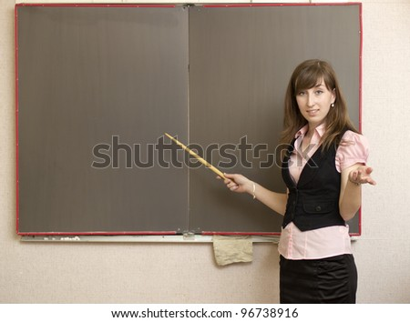 The young woman with a pointer at school boards - stock photo