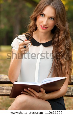 The young woman writes something in her planner - stock photo