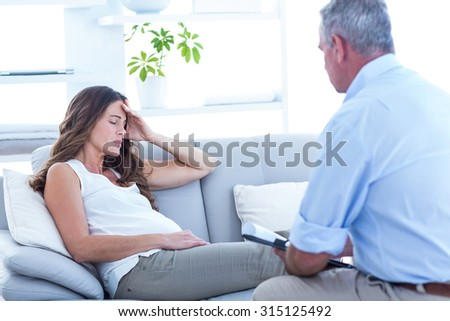 Thearapist advising to pregnant woman relaxing on sofa