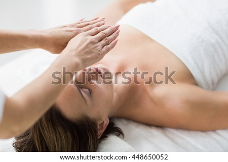 Thearapist performing reiki on young woman at spa - stock photo