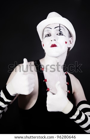 theater actor in makeup and a white hat on a black background - stock photo