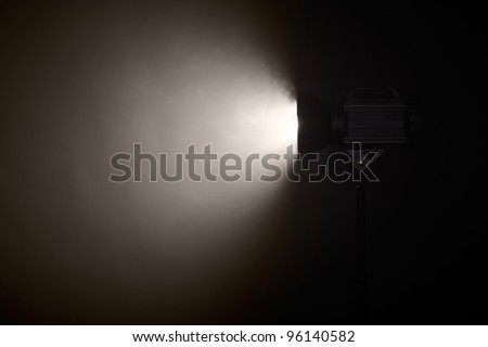 Theater spotlight over black background - stock photo