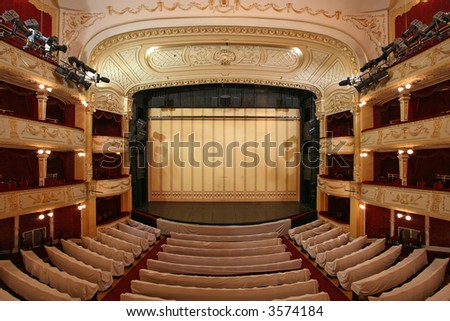 Theater stage with gold safety curtains and  empty chairs in the foreground - stock photo
