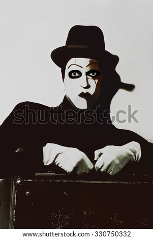 Theatrical actor with dark makeup on her face with a suitcase close up - stock photo