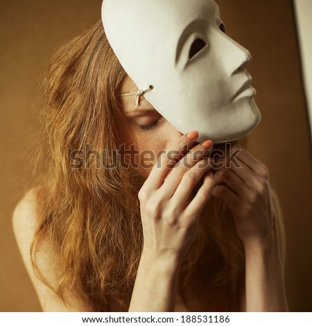 Theatrical actress: Vintage emotive portrait of a beautiful fashionable red-haired model with a white venetian mask - volto bianco. Natural make-up. Close up. Retro style. Studio shot with daylight - stock photo