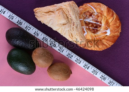 Theme of dietary contrast of products, fruit against rich rolls. - stock photo