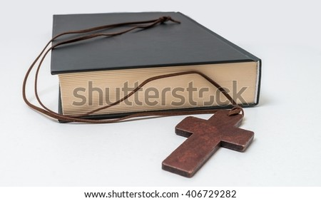 Theology concept. Bible book and brown crucifix on necklace. - stock photo