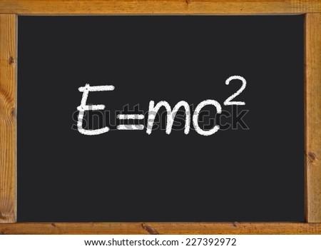 Theory of relativity (E=mc2) written on a chalkboard - stock photo