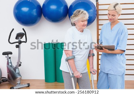 Therapist and senior woman looking at clipboard in fitness studio - stock photo