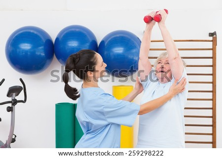 Therapist helping senior woman fit dumbbells in fitness studio - stock photo