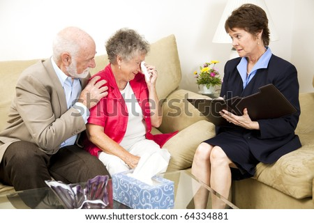 Therapist helps a senior woman suffering from depression.  Could also be grief counseling. - stock photo