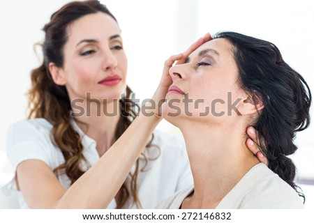 Therapist hypnotizing her patient on white background - stock photo