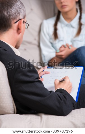 therapist is taking notes during therapy session