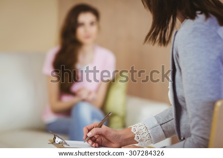 Therapist listening to her patient in therapists office - stock photo