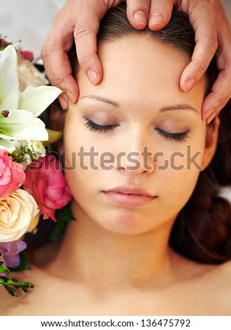 Therapist making different face massage with flowers near by
