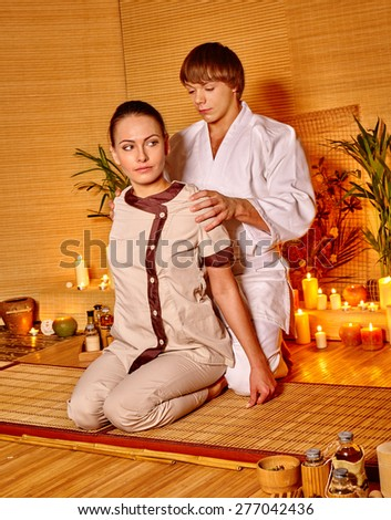 Therapist man giving Thai stretching massage to woman.Sitting on his lap - stock photo