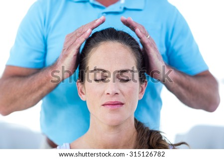 Therapist performing reiki on young woman at home