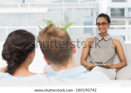 Therapist smiling at couple on the couch in therapists office - stock photo