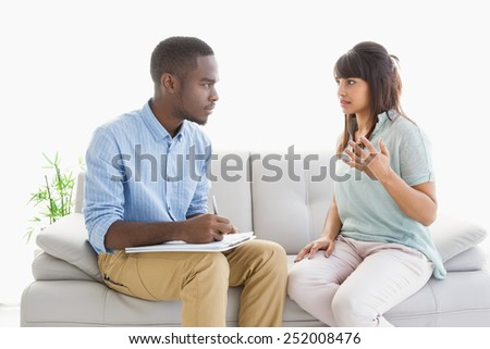 Therapist taking notes on his patient at therapy session - stock photo