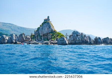 There are many rocky islands along the coast of Budva riviera, Mali Katic in Petrovac is one of them, Montenegro. - stock photo