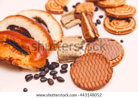 There are Pieces of  Roll with poppyseed,Cookies,Halavah,Chocolate Peas,Tasty Sweet Food on the White Background