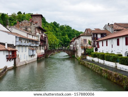 There are traditional white houses along the rapid river in the Basque mountainous town. - stock photo