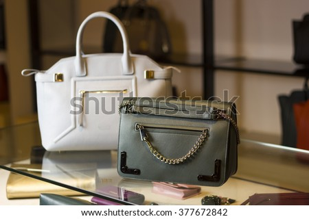There are two handbags on a glass shelf in the store. One bag is green or khaki, the second bag is white. They are made of leather. - stock photo