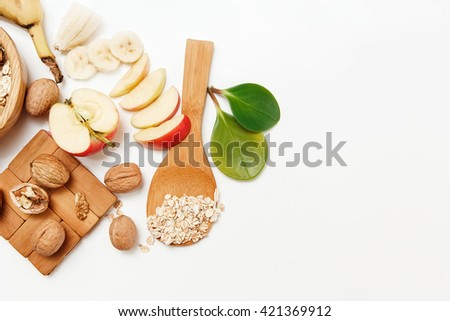 There are with Walnuts and Rolled Oats in the Wooden Plates with Sticks of Cinnamon,Wooden Support,Spoon,Green Leaves,Healthy Fresh Organic Food on the White Background,Top View - stock photo