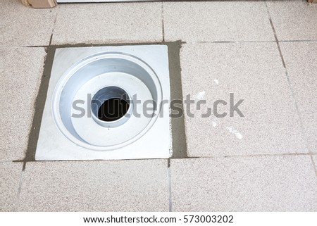 there is a sewer drain in the ground with cement fattene