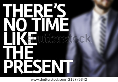 There's no Time Like the Present written on a board with a business man on background - stock photo