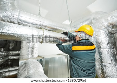 Thermal insulation. Female insulation worker isolating industrial pipe with glass wool and foil - stock photo