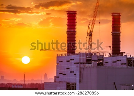 Thermal power plant in sunset - stock photo