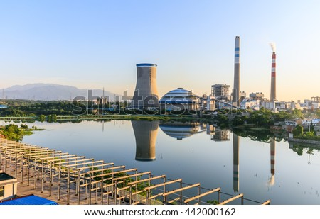 Thermal power plant reflection in a lake with blue sky, industry landscape