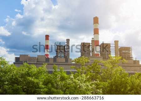 Thermal power plant with chimneys in the natural environment and flourishing woods in foreground.