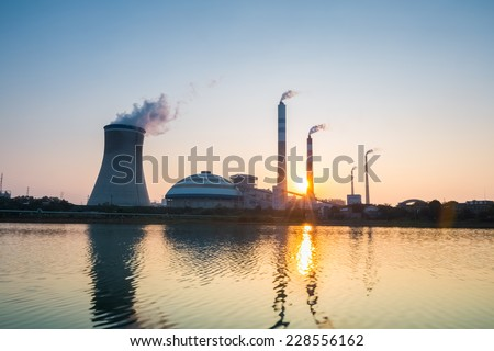 thermal power plant with the setting sun , industrial landscape  - stock photo