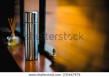 Thermo flask in the kitchen with decoration, Aluminum mug - stock photo