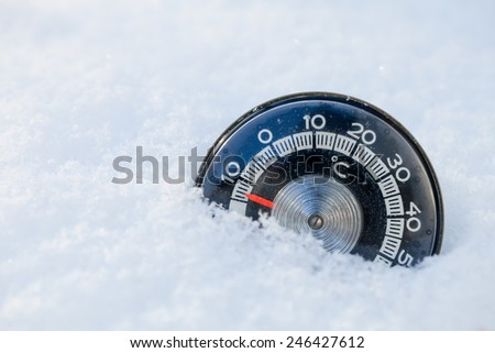Thermometer in the snow shows low temperature - stock photo