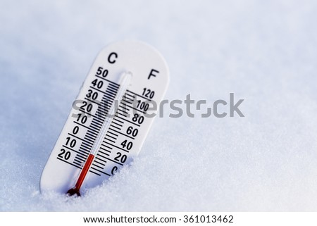 Thermometer in the snow with focus on the red.