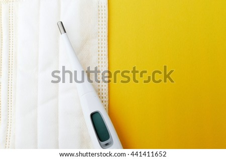 thermometer on a medical / face mask with yellow background the concept of prevention of virus/bacteria  - stock photo