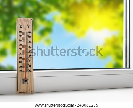 thermometer on the windowsill on the background of the summer heat - stock photo