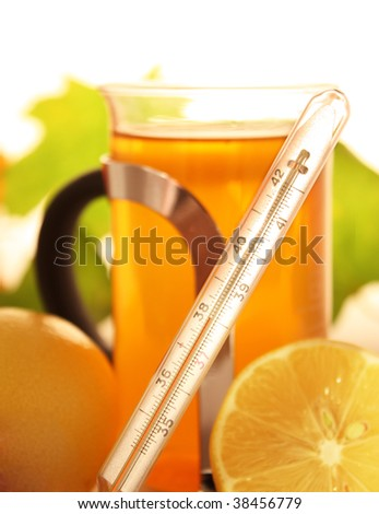 Thermometer with hot fever and tea with lemons on background - stock photo