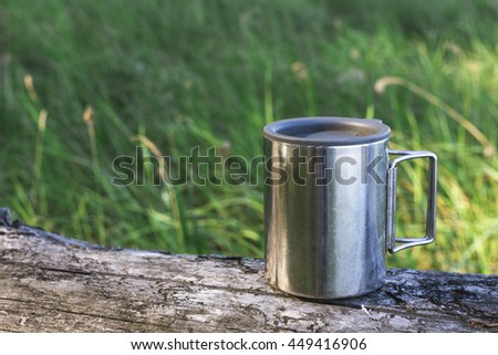 Thermos cup of coffee on wood with nature on background. Tourism and travel