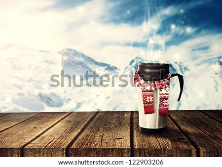 thermos with scarf on wooden table - stock photo