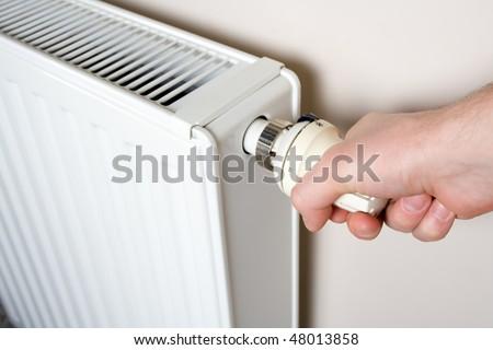 Thermostat adjustment. Man's hand adjusting radiator temperature. - stock photo