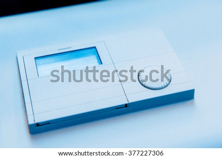 Thermostat closeup detail on blue technological background - stock photo