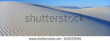 These are sand dunes in the morning. There are lines in the sand that form a pattern from the wind. - stock photo